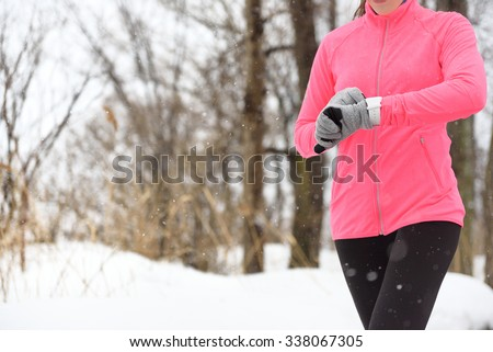 Runner using smartwatch jogging in snow trail in forest. winter weather closeup. Female athlete checking her cardio with a heart rate monitor during workout outside in running park. - stock photo