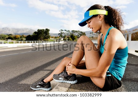 Runner with ankle injury has sprained and strained ankle, painful expression. typical road running problem associated with shoe choice - stock photo