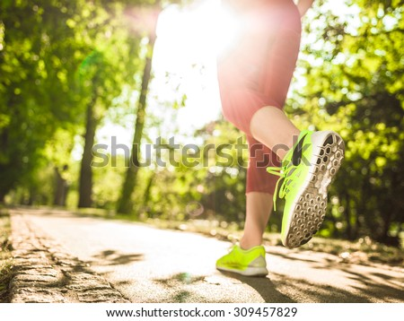 Runner woman feet running on road closeup on shoe. Female fitness model sunrise jog workout in the sunny park outdoors. Sports healthy lifestyle concept. - stock photo