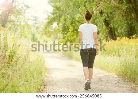 Runner woman jogging outdoors. Rear view. Healthy lifestyle and fitness concept. - stock photo