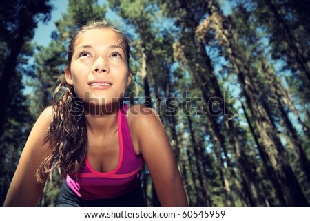 Runner. Woman running in forest taking a break from working out. Beautiful young female athlete - copy space. - stock photo
