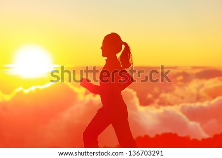 Runner woman running in sunshine sunset. Fitness athlete training trail running marathon in mountains above the clouds in beautiful mountain landscape. Female in jogging in silhouette. - stock photo