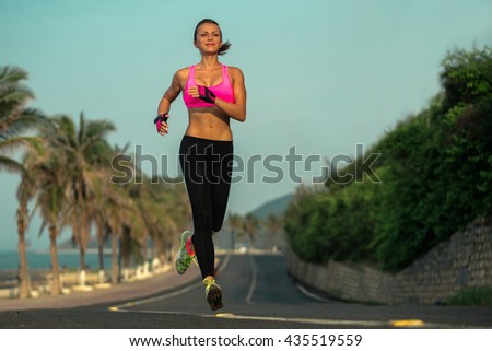 Runner woman running on beach road in beautiful nature. Female sport fitness model jogging training for marathon during outdoor workout. - stock photo