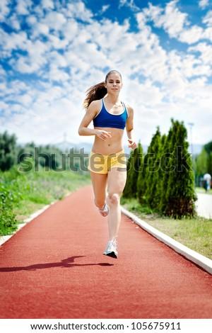 runner - woman running outdoors training for marathon run. Beautiful fitness model in her 20s. - stock photo