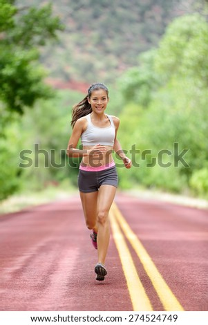 Runner woman running training living healthy fitness sport lifestyle. Active female athlete jogging outdoors happy with aspirations. Beautiful mixed race Asian Caucasian girl in full body length. - stock photo
