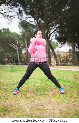 Runner woman stretching and getting ready to do exercise in a park outdoors
