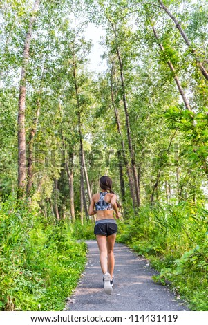 Runner woman training cardio running on forest path in city park in summer nature. Back of girl jogging living a healthy active lifestyle wearing sports activewear clothing working out full length. - stock photo