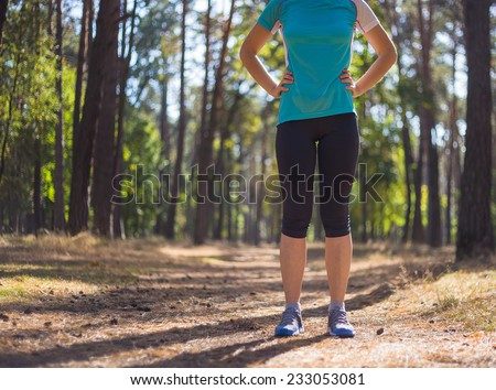 Runner woman training on forest road in beautiful nature. Caucasian female sport fitness model jogging training for marathon during outdoor workout.