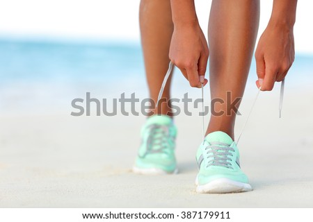 Runner woman tying laces of running shoes preparing for beach jogging. Closeup of hands lacing cross training sneakers trainers for cardio workout. Female athlete living a fit and active life.
