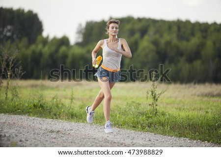 Runner woman with bottle of water , close-up. Beautiful fit female fitness model training and working out outside in summer at part of healthy lifestyle.