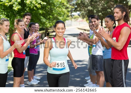 Runners applauding a racer in the park on a sunny day - stock photo