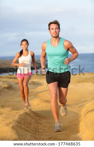 Runners couple jogging for fitness running in beautiful landscape nature outdoors. Young female and male sports athletes training cross-country trail running. Asian woman, Caucasian man,