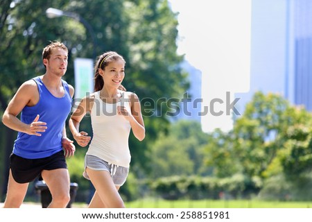 Runners jogging in New York City Central Park, USA. Healthy couple of new yorkers athletes running in summer sun working out a cardio exercise on Manhattan, United Sates of America. - stock photo