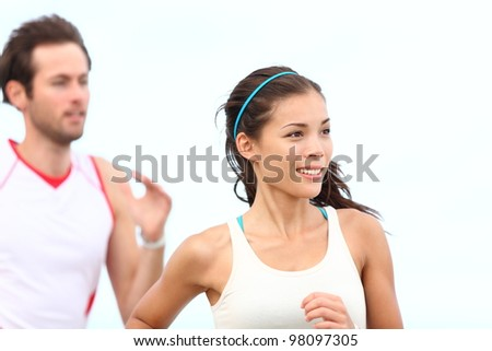 Runners jogging. Young couple running outside training for marathon. Asian woman sport model smiling happy with caucasian male runner in background. - stock photo