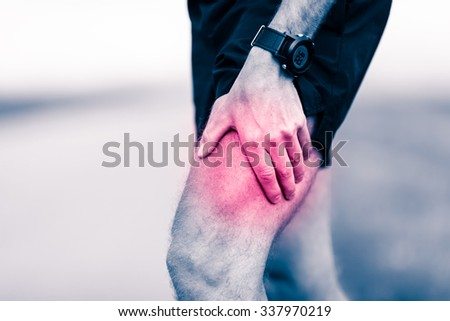 Runners leg pain, man holding sore and over trained painful leg muscle, sprain or cramp ache filled with red pink bright place. Injured over trained person when exercising or running outdoors. - stock photo