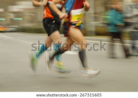 Runners legs on the road with panning blur - stock photo