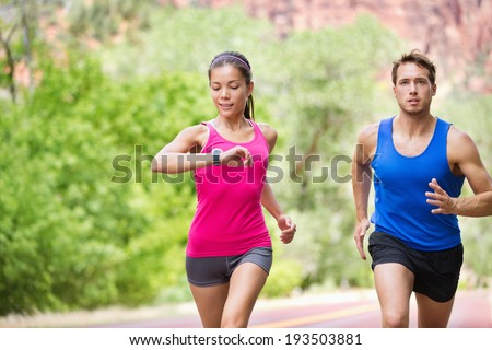 Runners - mixed multicultural couple training outside in nature. Fitness asian young smiling model checking time or pulse on heart rate monitor watch and male model jogging. - stock photo
