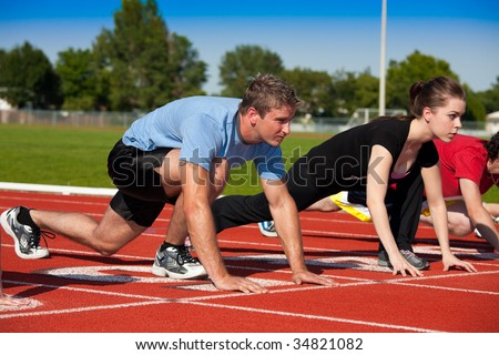 Runners on the starting line.   Selective focus on first runner. - stock photo
