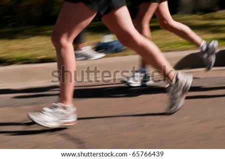 Runners - runners speed by (legs only) - panning and motion blur - stock photo