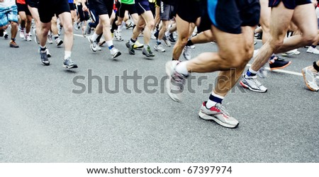 Runners running in city marathon, motion blur on sporty legs