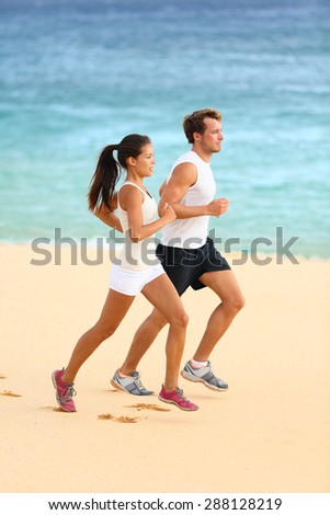 Runners running on beach. Jogging couple training on beach in full body length living healthy active lifestyle. Asian runner woman and fit male fitness athlete on run. - stock photo