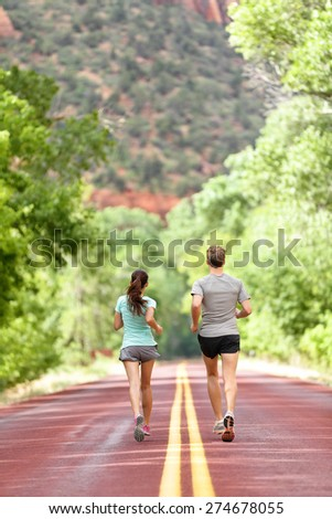 Runners running on road in nature away from camera. Couple, woman and man jogging for a run outside in amazing mountain landscape. Full body length rear view of back. Fitness and healthy lifestyle. - stock photo