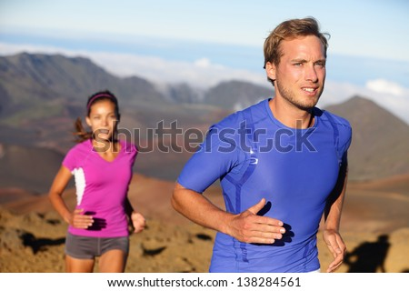 Runners trail running athletes. Young fitness runner couple training trail running cross-country run for marathon. Fit man in compression t-shirt and woman model working out together. Multiracial. - stock photo