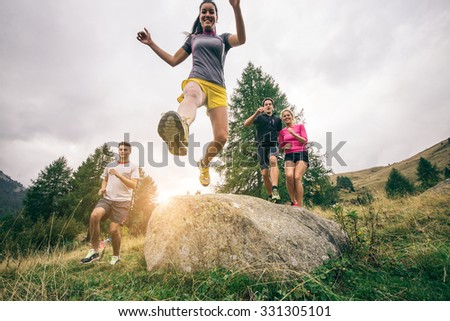 Runners training on a off road track - Group of hikers walking in the nature at sunset - Friends taking an excursion on a mountain - stock photo