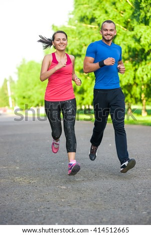 Runners training outdoors working out. City running couple jogging outside. City sport training in green park. - stock photo