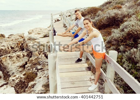 Runners. Young couple exercising and stertching on beach - stock photo