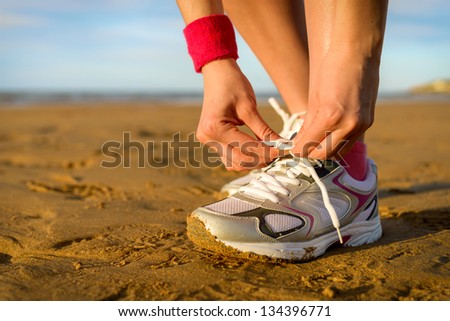 Running and jogging exercising concept. Woman tying laces before training on beach. Unrecognizable caucasian girl wearing sport shoes. - stock photo