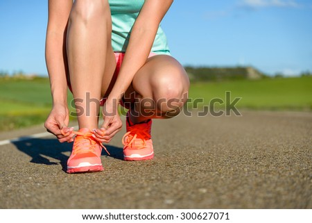 Running and sport concept. Female athlete tying sport footwear laces on road before training. - stock photo