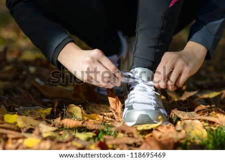 Running and sport concept.Sportswoman hands tying shoelaces. Female athlete getting ready for running in park outside and doing exercise. - stock photo