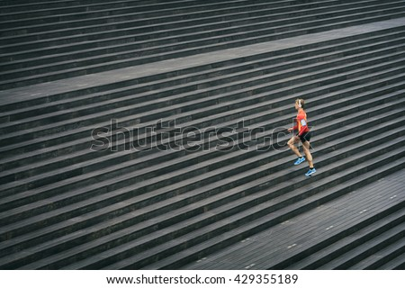 Running athlete jogging outdoors listening to music on cell phone. Sport outside on wooden staircase - stock photo