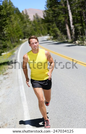 Running athlete man jogging on nature road in forest mountain. Full body male adult on a jog in summer. - stock photo