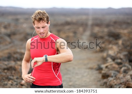 Running athlete man looking at smartwatch heart rate monitor GPS smart watch. Runner listening to music in earphones. Athlete resting tired after training on Big Island, Hawaii, USA. - stock photo