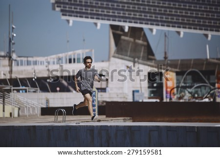 Running athlete man. Male runner sprinting during outdoors training. Athletic fit young sport fitness model in his twenties in full body length on road outside in city urban - stock photo