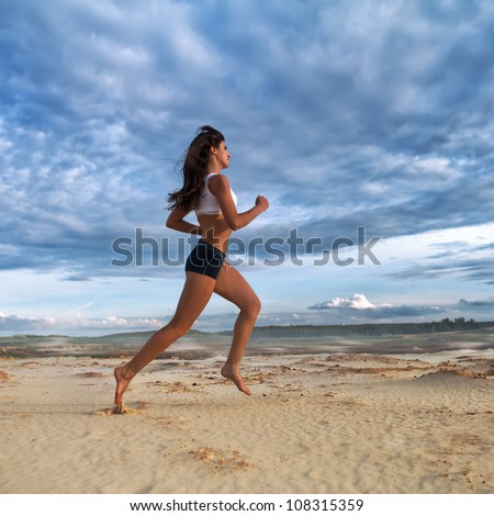 Running barefoot woman. Female runner jogging during outdoor workout on sand at evening. Beautiful  Fitness model outdoors. - stock photo