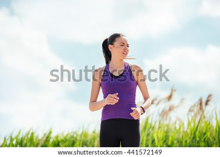 Running beautiful young woman on nature background. Hard workout and exercises. Sport