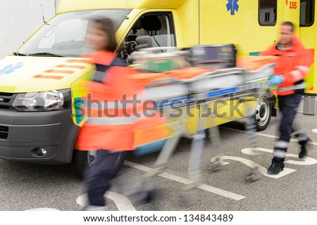 Running blurry paramedics team with stretcher and ambulance car - stock photo