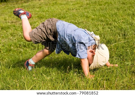 Running boy fall down in park - stock photo