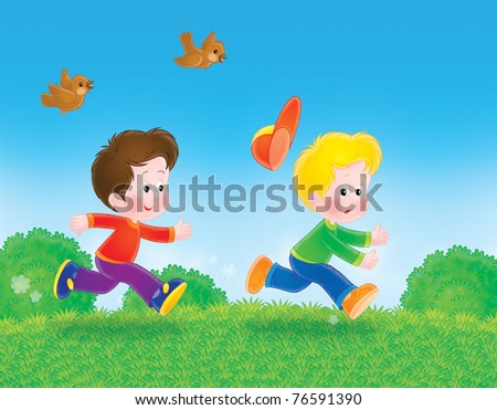 running boys play tag on the green grass - stock photo