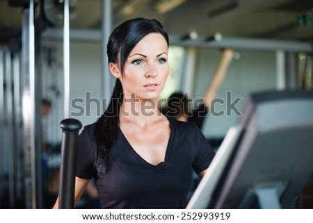 Running brunette in black t-shirt at gym. - stock photo
