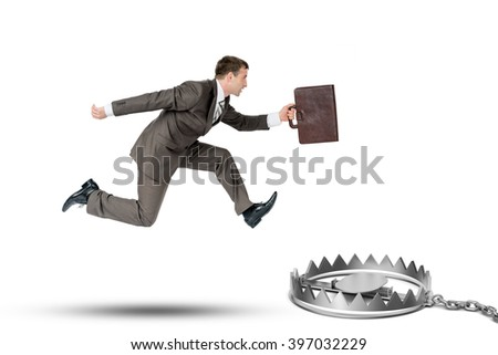 Running businessman with bear trap