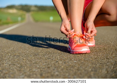 Running challenge concept. Female athlete tying sport footwear laces on road before training. - stock photo