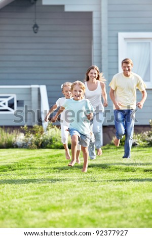 Running children and parents outdoors - stock photo