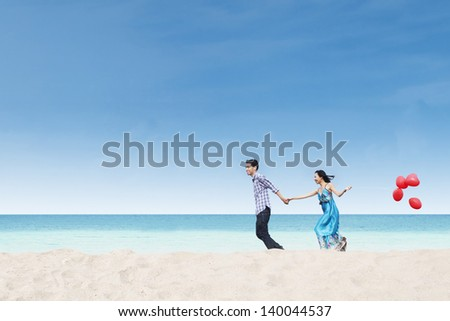 Running couple at beach holding balloons under blue sky