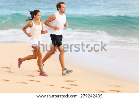 Running couple jogging on beach exercising and jogging training. Sport runners working out on summer beach. Asian woman, Caucasian man. - stock photo
