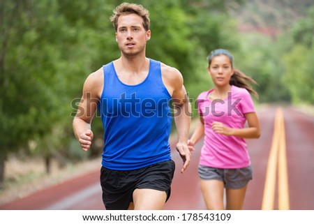 Running couple jogging on road. Runners training for marathon run sprinting. Active young multiracial couple in active healthy lifestyle concept. Asian woman and fit caucasian man fitness model. - stock photo