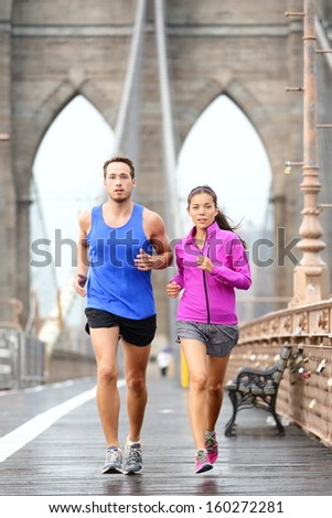Running couple jogging training for New York marathon. Runners in rain outside. Asian woman and Caucasian man runner and fitness sport models jogging on Brooklyn Bridge, New York City, USA - stock photo